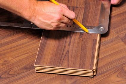 Laming bzw. Parkett verlegen. Bodenbelag aus Holz. Verlegen eines neuen Bodens. Das Parkett wird geschnitten und verlegt.