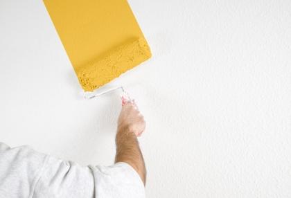 Malerarbeiten mit einem großen Pinsel. Gelb goldene Farbe auf einer weissen Wand. Schöne Farben mit einem professionellen Anstrich. Maler , Malermeister , Trockenbau