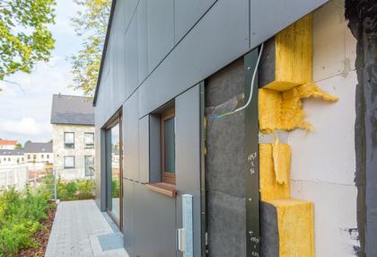 Fassendämmung und Hausdämmung an einem Neubau . Gelbe Farbe der Dämmwolle sticht aus dem dunklen grauton heraus. Renovierung Sanierung Ausbesserung durch Malermeister