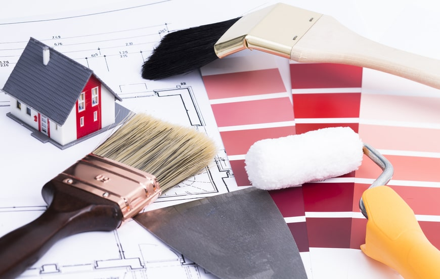 Saubere Pinsel und Spachteln liegen auf Arbeitsunterlagen. Eine Farbauswahl von verschiededen roten Farben. Ein Miniatur Haus in weis roten Anstrich ist zu sehen. Unter dem Haus befindet sich ein Lageplan bzw. Projektplan